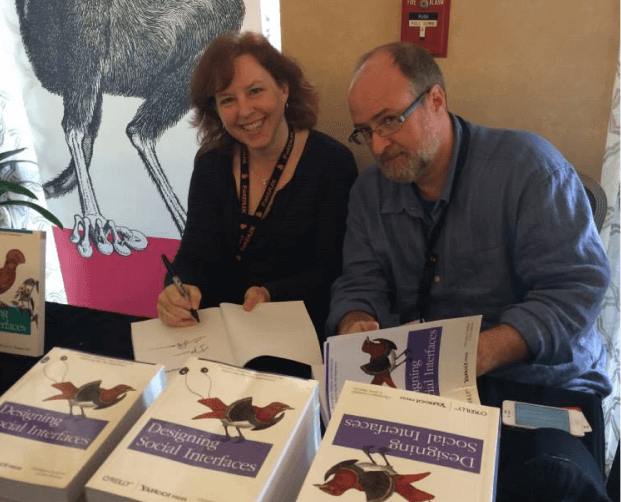 Picture of Christian sitting behind a table at a book signing, next to his co-author.